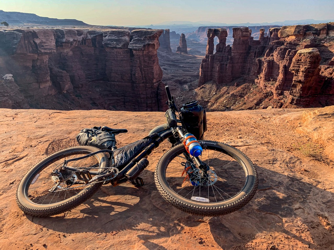 mountain bike laying on the ground on the edge of the canyon with spires and arches in the distance