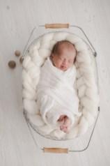 Newbornfotografin Neugeborenenfotos Babyfotos Fotografin Körbchen weiß wolle Holz Zunge raus sanft nordisch Michaela Klose