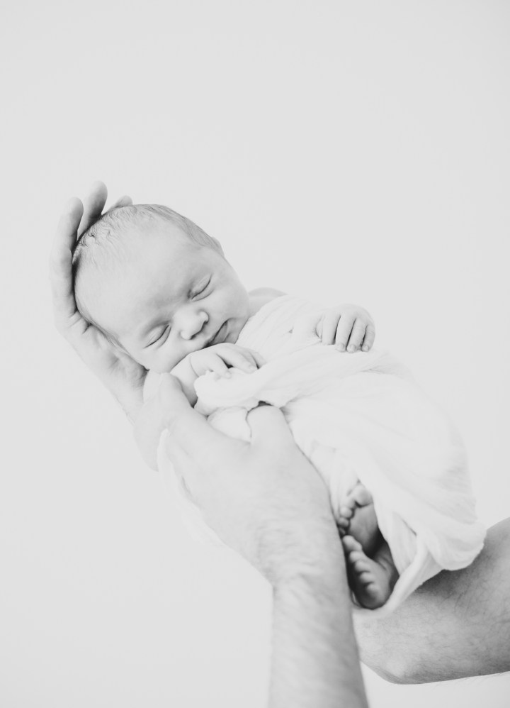 Schwarz Weiß Babyfoto Baby auf Arm Papa hält Baby zeitlose Babyfotos