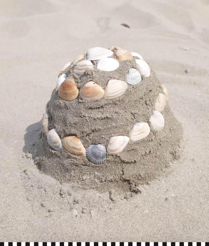 Ein hübsch mit Muscheln dekorierter Sandkuchen - aus echtem Sand