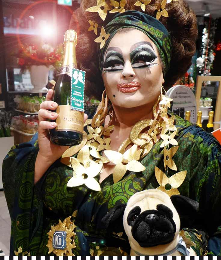 Freifrau von Kö mit Heinemann-Haus-Champagner