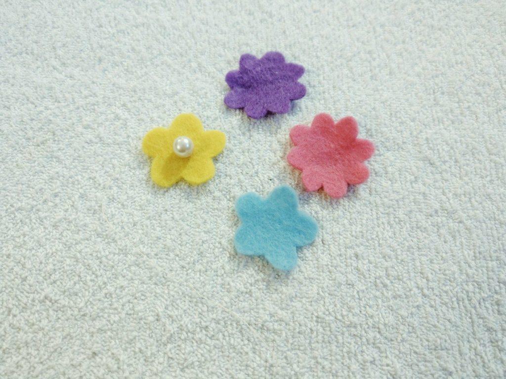Die Filzblumen für das Einhorn Oberteil werden mit Perlen verschönert.