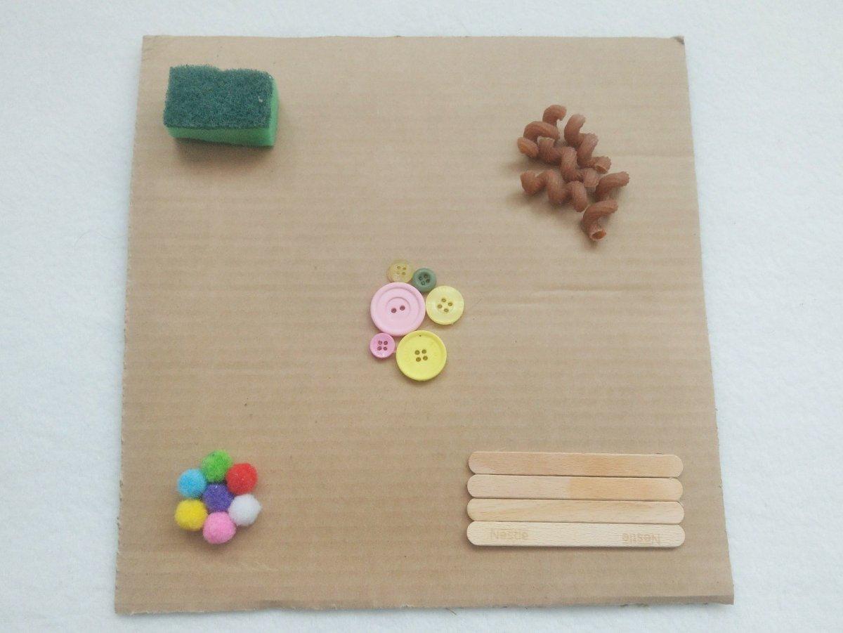 Mit Heißkleber verschiedene Materialien auf einen Karton kleben und schon habt ihr eine tolle Beschäftigung für kleine Kinder. Ein Sensorik Board einfach schnell selber machen.