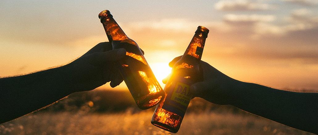Feierabend: Anstoßen mit zwei Bierflaschen in der Abendsonne