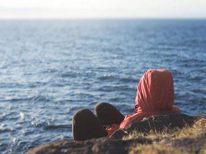An der Küste sitzen, weiter Blick aufs Meer