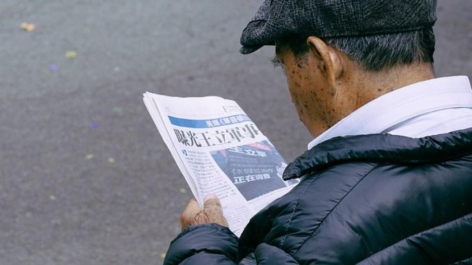 Zeitungsleser auf der Parkbank