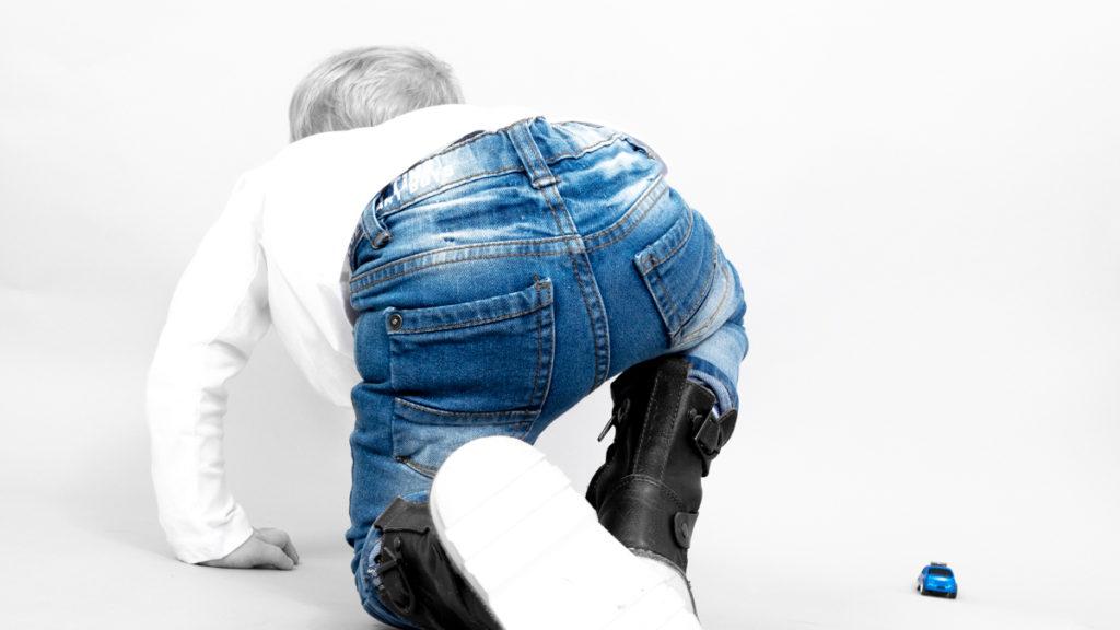 Blauwe jeans van peuter, kruipend uit beeld