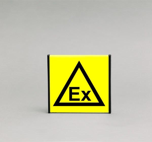 Sprogios aplinkos įspėjamasis ženklas, kurio išmatavimai yra 93x93mm, skirtas įspėti apie galima sprogimą patalpų viduje.