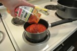 Pour the entire jar of sauce into the pot to begin heating.