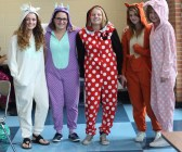 """MONDAY: Sophomores Rebecca Taplin, Kylie Taplin, Karli Little, Katie Schnieder, and freshman Emma Hilgart-Griff show their school spirit in onesies. Hilgart-Griff explained, """"We are all swimmers!"""" on the women's swim team. Photo Credit / Hannah Pittman"""