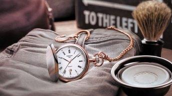 Reloj de bolsillo Tissot en color dorado con plateado sobre un pantalón de mezclilla