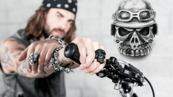 Portada de un hombre en una moto con los anillos y pulseras en forma de calavera Bomberg