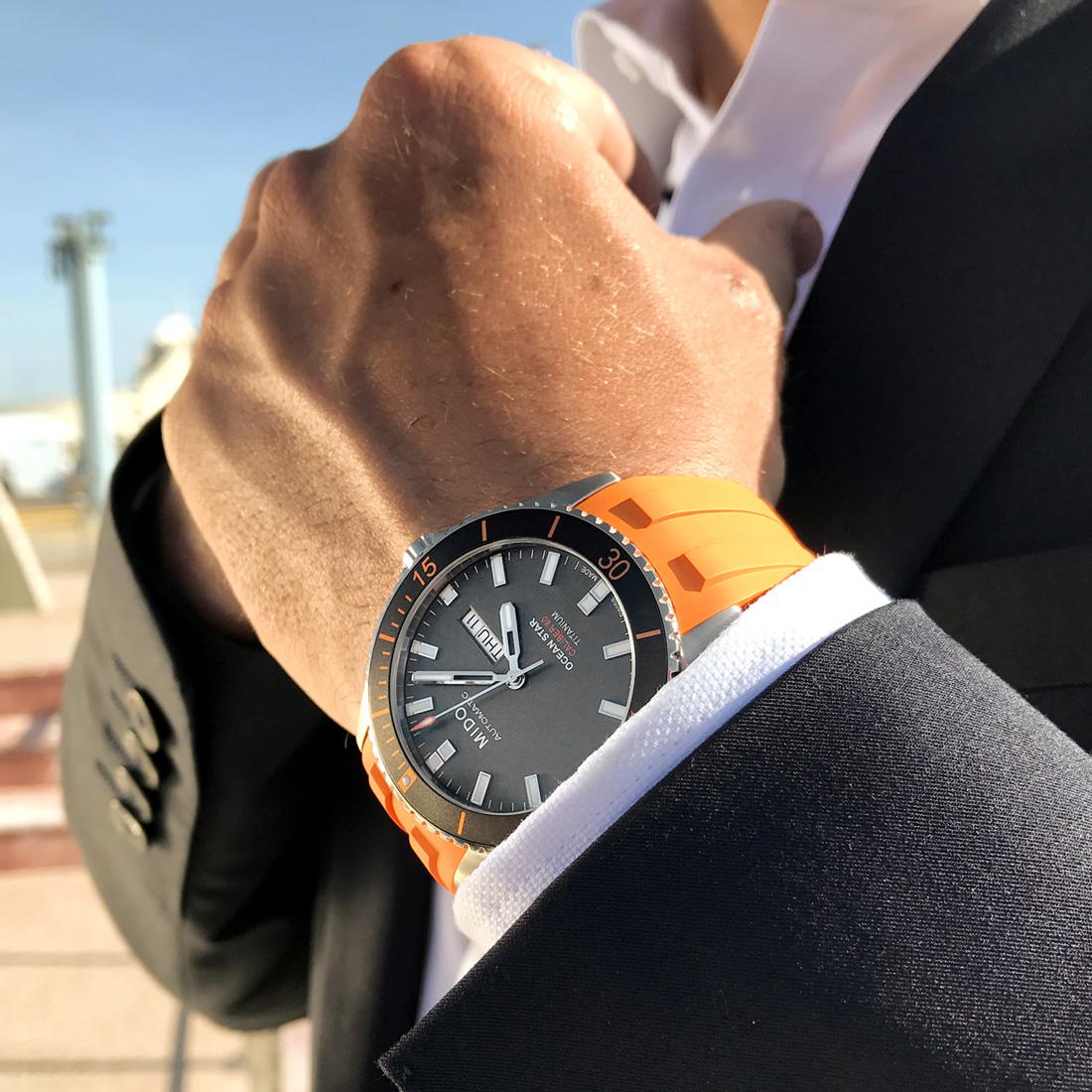 Hombre con el reloj MIDO con correas naranjas y caratula plateada