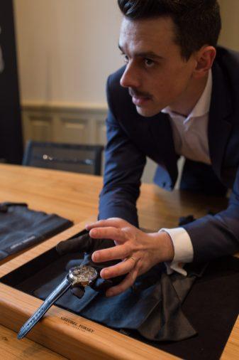 Greubel Forsey con un reloj en la mano explicando los detalles de su funcionamiento