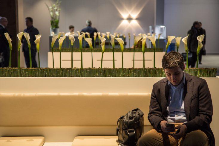 Hombre con un celular sentado en el evento Baselworld