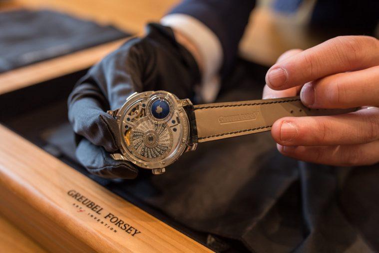 Reloj plateado con correas en negro tomado por unas manos