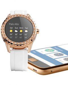 Reloj con correas blancas y caratula dorada con el dial negro junto a un celular dorado