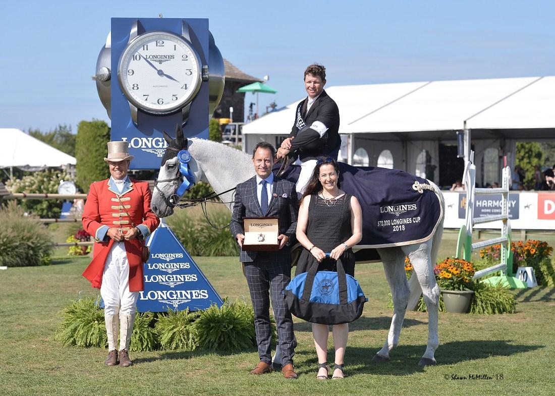 Indra Van De Oude Heihof y Shane Sweetnam son presentadas top award en el Longines Cup por Pascal Savoy
