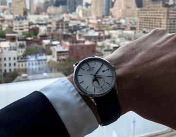 EDOX colaboracion Artworth Brothers en NY mano izquierda mostrando reloj con ciudad de día