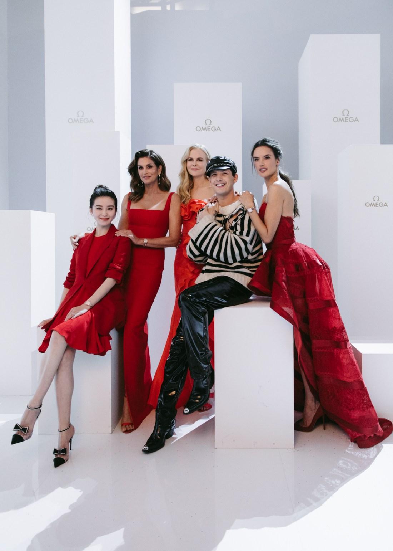 Modelos con vestido de color rojo en evento de OMEGA con hombre de rayas
