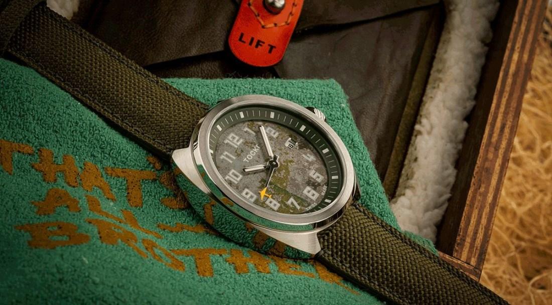 Reloj That's All Brother en color verde pálido con detalles plateados sobre una manta verde