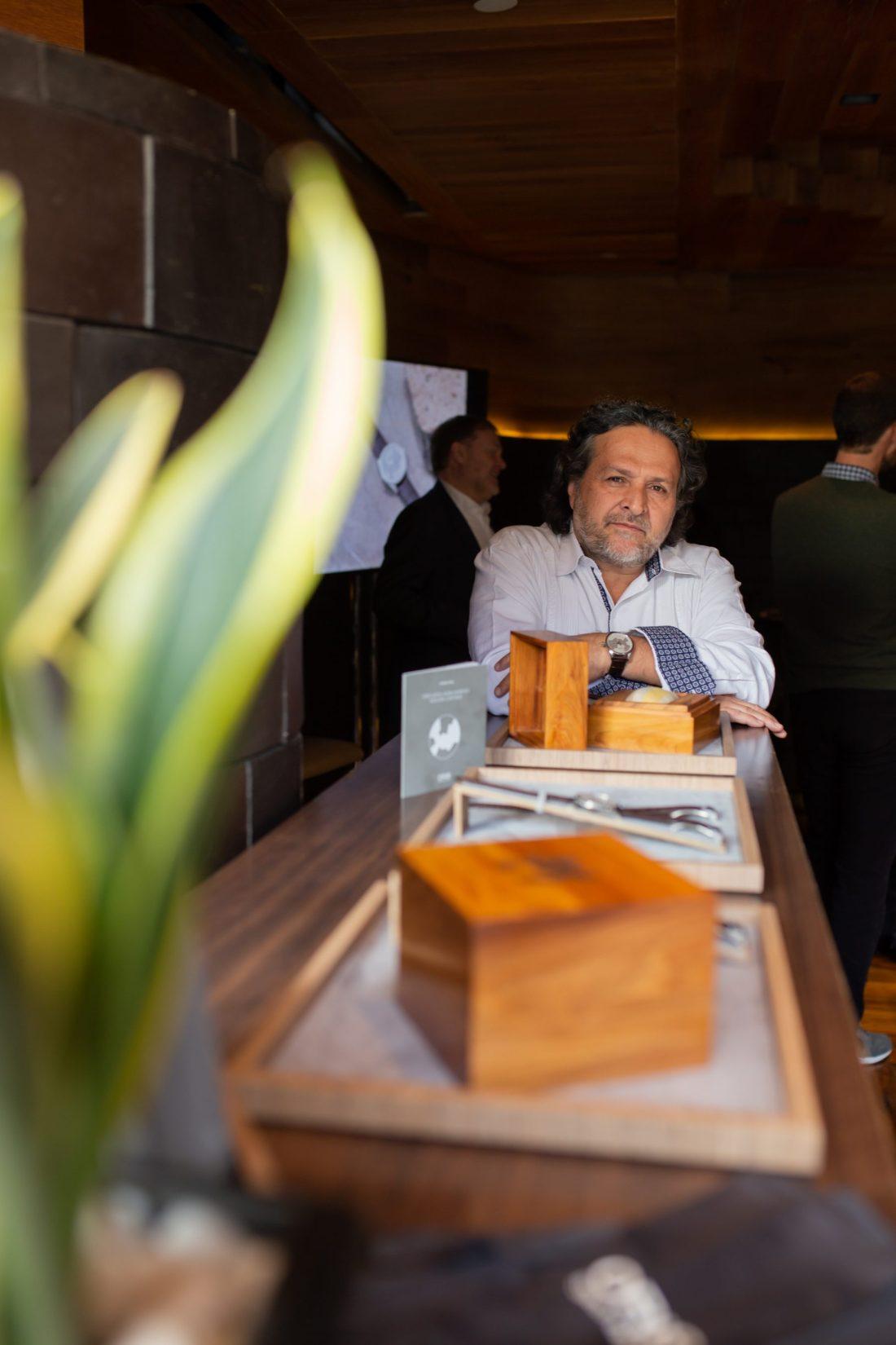 Adán Paredes con camisa blanca sentado jutno a los relojes Oris Artix
