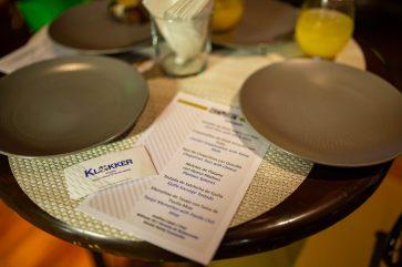 Carta del menú del evento sobre una mesa de madera y platos al rededor