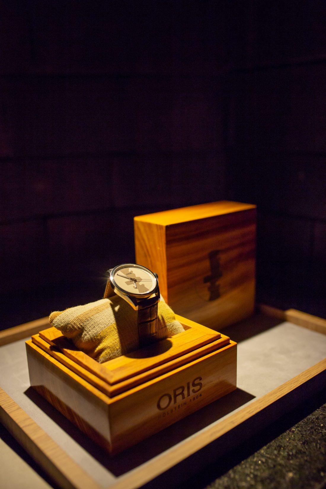 Reloj Oris Artix dentro de una pequeña caja de madera acolchonada en la oscuridad