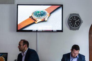 Alberto Rodríguez y David Weber sentados con una pantalla y un reloj en la pared