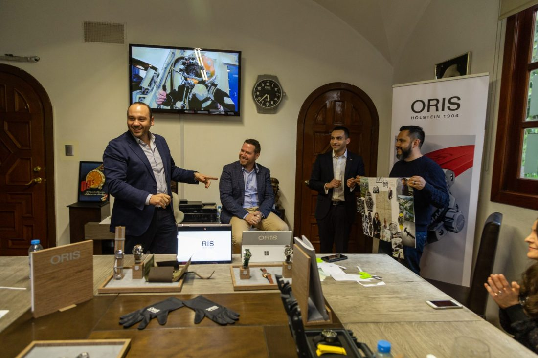 Personas exponiendo el carte elaborado con recortes frente a los directivos de Oris