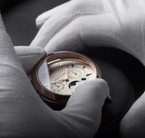 Manos con guantes blancos sosteniendo una caratula de un reloj