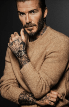 Beckham con sueter en color camel usando un reloj Tudor
