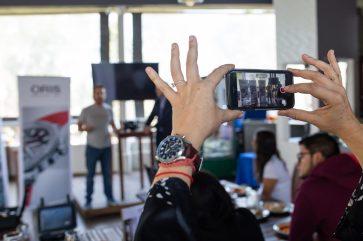 Mujer grabando con celular durante la conferencia a Gerardo del Villar