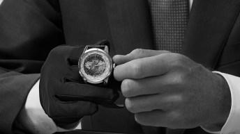 Imagen en blanco y negro mostrando las manos con un guante de un hombre tomando un reloj