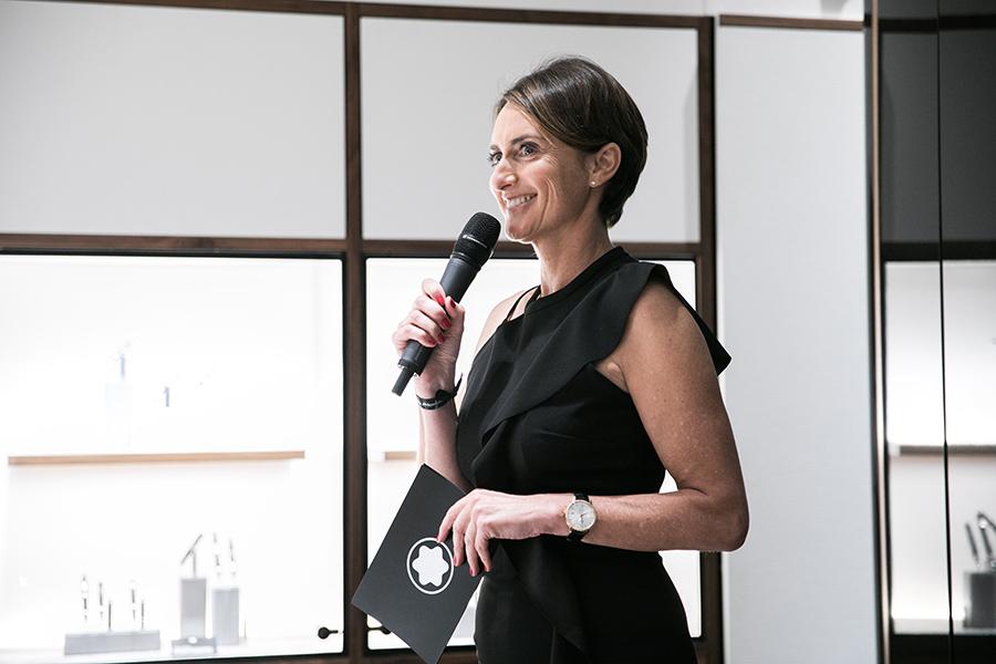 Delphine Favier vestida en color negro hablando con un microfono y unas tarjetas en la mano