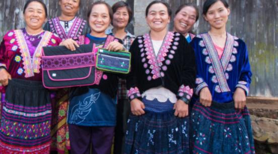Mujeres con vestimenta indigena y un par de bolsas de diversos colores