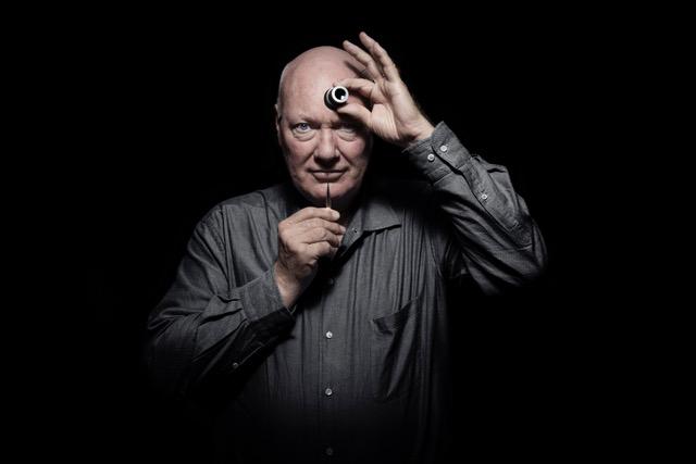 Jean-Claude con camisa negra con unos artefactos en las manos y fondo negro