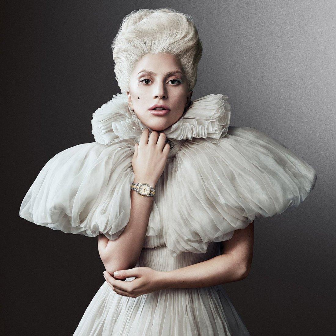 Lady Gaga con vestido blanco y usando un reloj plateado con detalles en amarillo