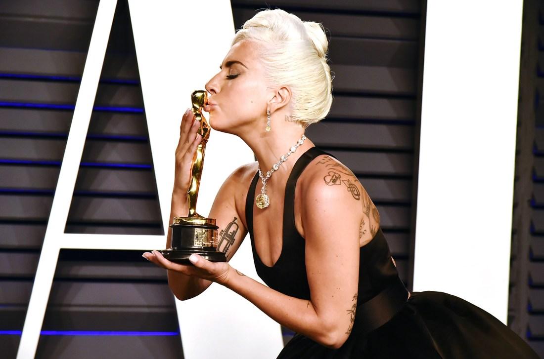 Lady Gaga con vestido negro y premio Oscar en las manos besandolo