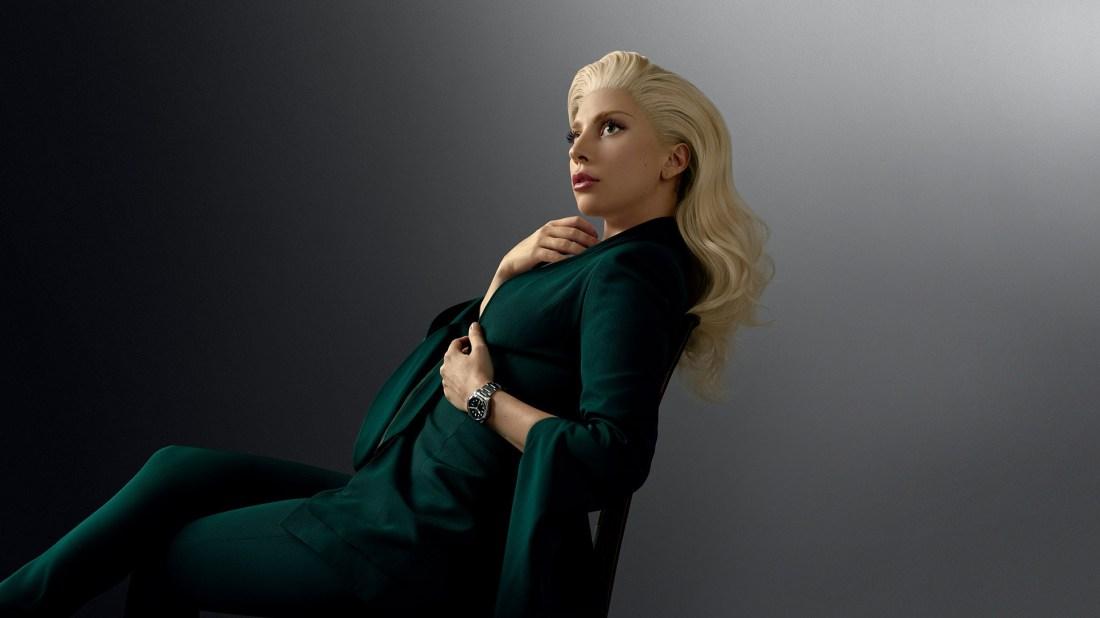Lady Gaga con un traje en color verde sentada usando un reloj Tudor en la muñeca