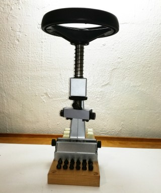 Llave de volante bergeon volante negro y estructura en plateado con base de madera de frente