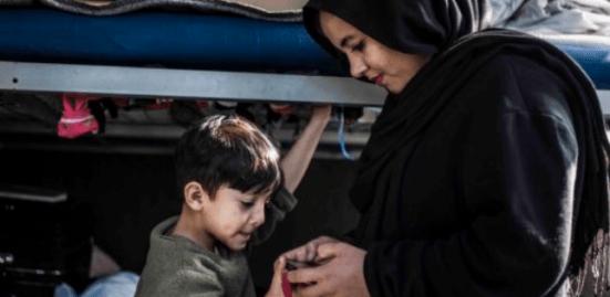 Mujer vestida de negro junto a un niño sosteniendo algo en las manos