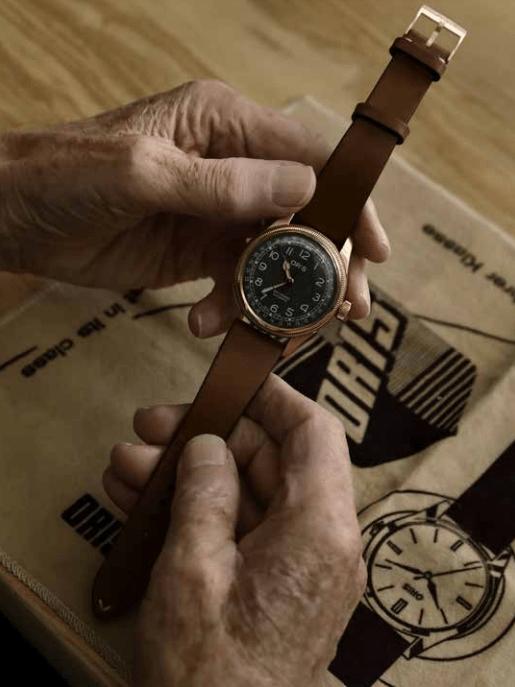 Oris vintage con correas en color cafe con detalles en color bronce y dial en color negro tomado por unas manos