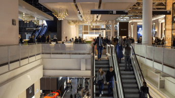 Personas subiendo y bajando escaleras en el evento Baselworld