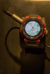 Reloj Casio en color gris con detalles en color rojo con un mapa al centro