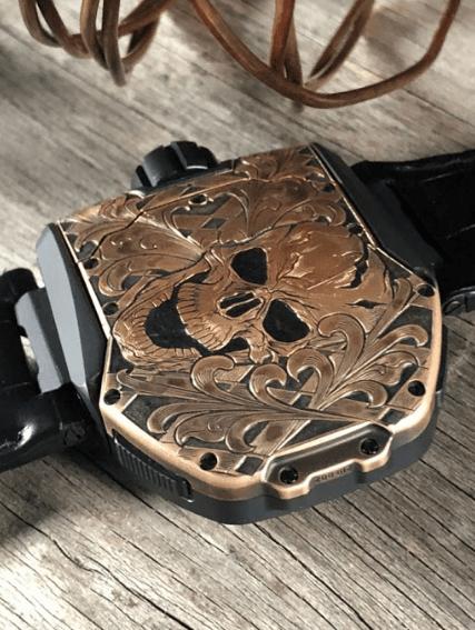 Reloj negro con la figura de una calavera en color dorado