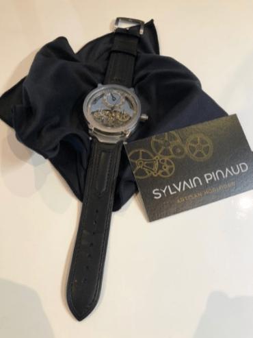 Reloj con correas en color negro con detalles en plateado sobre una tela negra