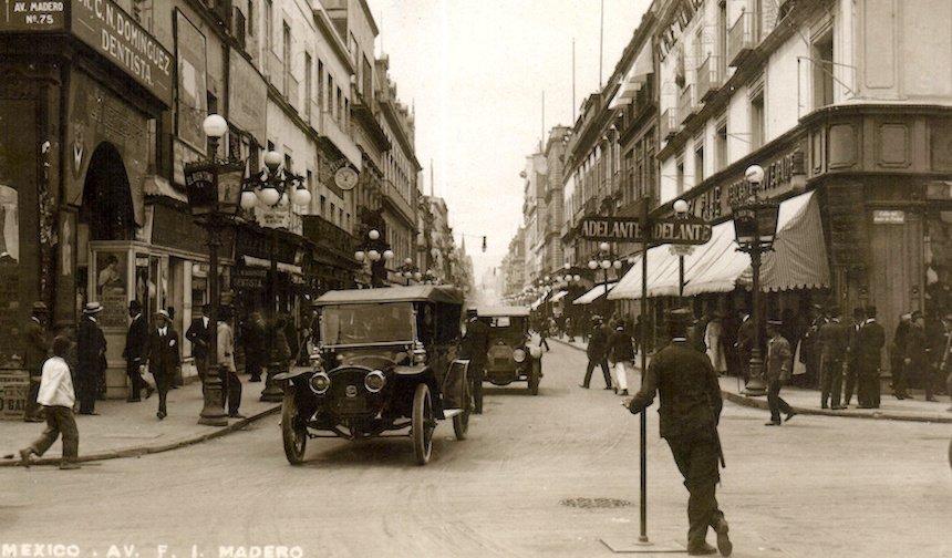 Imagen antigua de personas y automóviles transitando por la calle Madero