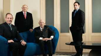 Hombres con traje negro en una oficina, dos estan sentados en un sillón azul y dos están de pie