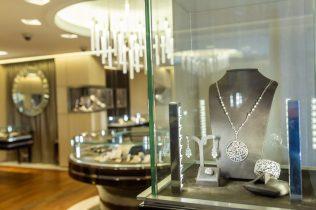 Collar, pulsera, aretes y anillo dentro de una vitrina con pequeñas lámparas